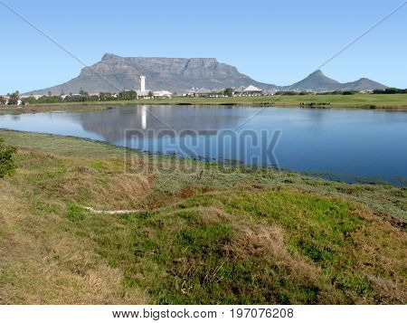 FROM CAPE TOWN SOUTH AFRICA, MILNERTON LAGOON, WITH REFLECTIONS OF TABLE MOUNTAIN AND THE LIGHT HOUSE IN THE WATER
