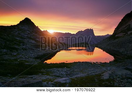 Sunset in mountains near lake. Sunlight reflected on mountain tops. Golden light from sky reflected in a mountain lake. Ergaki