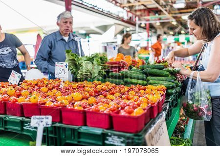 Montreal, Canada - May 28, 2017: Man Selling Produce By Fruit Stand With Woman Buying Cucumbers At J