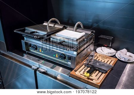 Electric double-stove operated waffle maker for breakfast serving on stainless counter at luxury hotel. Durable square waffle machine for commercial use.