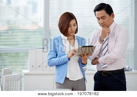 Pensive Vietnamese business people analyzing information on tablet computer
