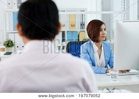 Pretty Vietnamese business lady concentrated on work in office