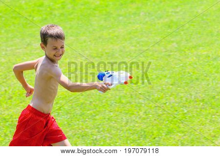 Child playing with water gun at hot summer day