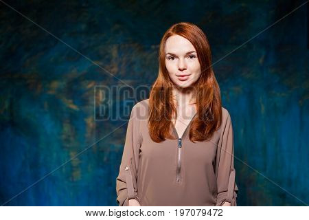 Red-haired cute girl in brown blouse. beauty model girl with luxurious red hair. hairstyle. holiday makeup.
