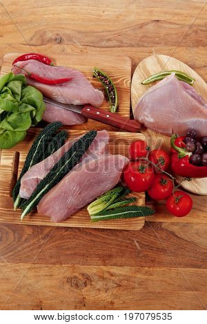 fresh raw turkey meat steak fillet with vegetables kale tomatoes lettuce red hot chili pepper and dark olives on cutting board over wooden table