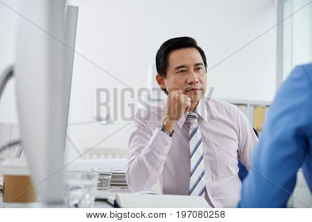 Vietnamese middle-aged businessman attentively listening to his coworker