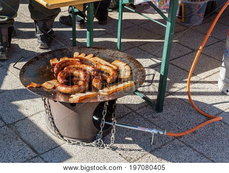 Frying sausages and tasty pieces of lard on an outdoor barbecue propane disc cooker. Sausages are traditionally prepared at all gastronomic festivals.