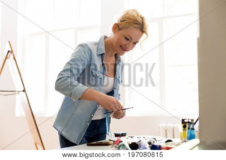 art, creativity and people concept - happy smiling woman artist with easel, paint brush and colors painting at art studio