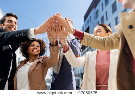 business, education and corporate concept - international group of people or students making high five on city street