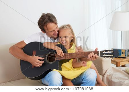 Father teaching his little daughter how to play guitar