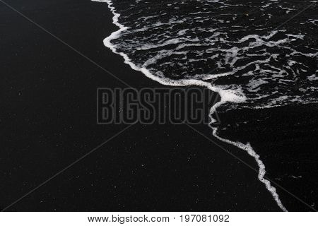 ocean foam on black sand volcanic texture