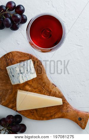 The glass of red wine, bunch of purple grapes, blue cheese and parmesan on the beautiful wooden plank of olive wood on the textured white background.
