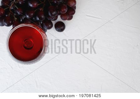 The glass of red wine and bunch of purple grapes on the white textured background. Copy space, top view.