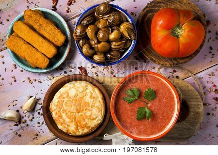 high-angle shot of some different spanish dishes, such as spanish omelet, gazpacho, caracoles en salsa, a recipe of escargots, or fish sticks on a rustic wooden table