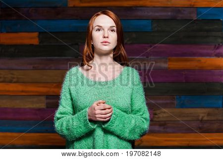 beautiful girl with red hair in greem pullover over colorful wooden background. beauty model woman with luxurious red hair. hairstyle. holiday makeup