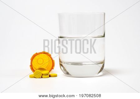 Pills and medication and a glass with water on a white background