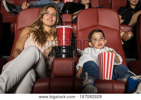 Beautiful young woman and her son watching a movie in a cinema theater during a date night