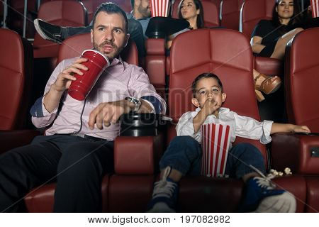 Handsome Hispanic young man and his son sitting in the movie theather and enjoying a film together