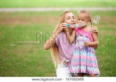Happy mother and daughter blowing soap bubbles