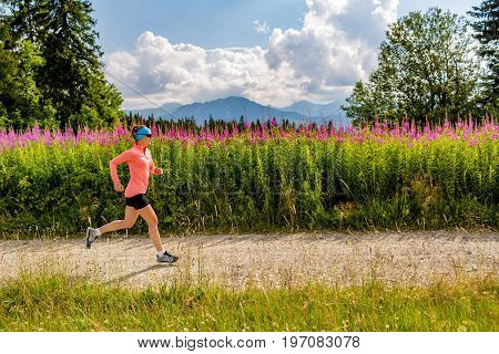 Young woman running in mountains on summer sunny day. Female athlete trail runner on country road. Sport and fitness concept outdoors in nature.
