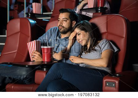 Pretty young woman holding her boyfriend's arm while watching a scary scene in a movie theater