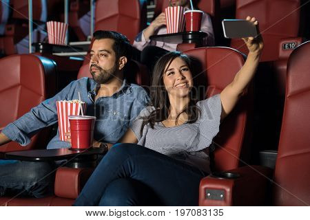 Cute young woman taking a selfie for her social media profile while she sits at the movie theater with her boyfriend