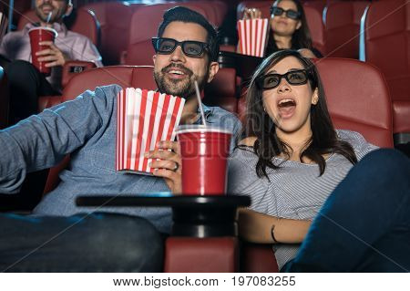 Portrait of a cute couple with 3d glasses watching a movie in the cinema theater and looking suprised