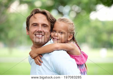 Portrait of happy father giving his daughter piggyback ride