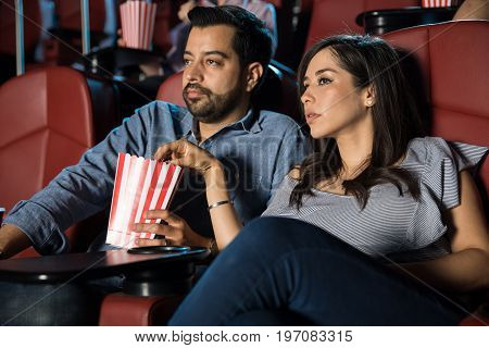 Good looking couple watching a thriller at the movie theater and eating some popcorn