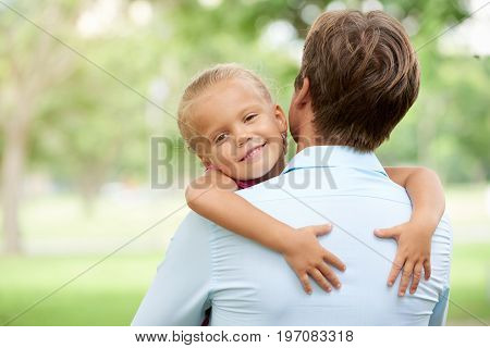 Cute smiling little girl hugging her father and looking at camera