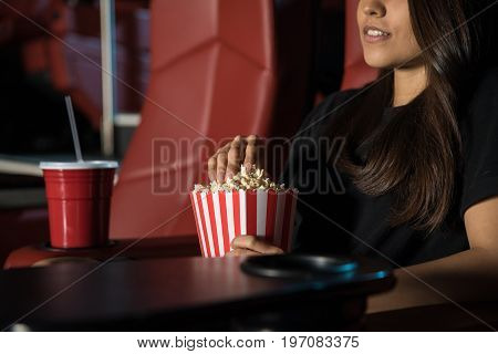Close up of a young woman watching a movie at the cinema theater while eating some popcorn