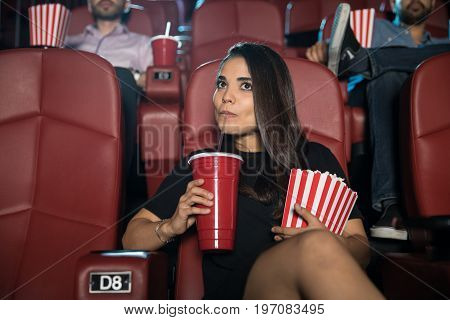 Portrait of a beautiful woman eating some popcorn and drinking soda while sitting in a movie theater