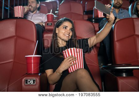 Pretty girl taking a selfie with her smartphone while watching a movie by herself at the cinema theater