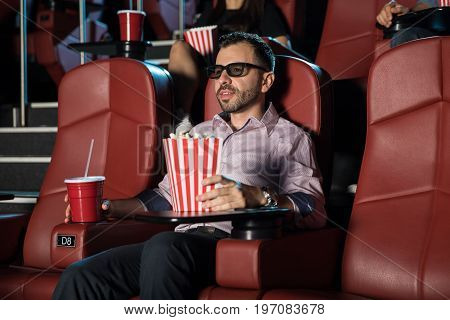 Portrait of a handsome young man wearing 3d glasses and watching a film at the movie theater