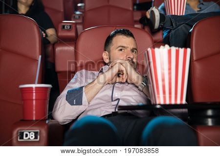 Portrait of a young Latin man watching a scary movie and trying to hide on his seat at the cinema theater