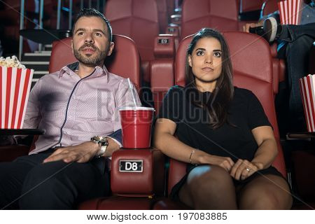 Nervous looking couple sitting next to each other at the movie theater on their first date