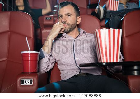 Portrait of a good looking young Hispanic man looking really bored while sitting by himself at the movie theater