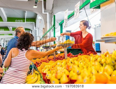 Montreal, Canada - May 28, 2017: Happy Smiling Woman Selling Produce By Fruit Stand With Sample Slic
