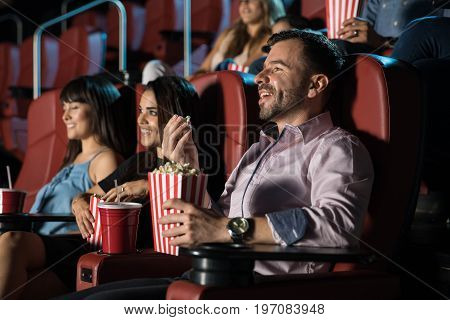 Crowd of young adults sitting in a movie theater and having a good time