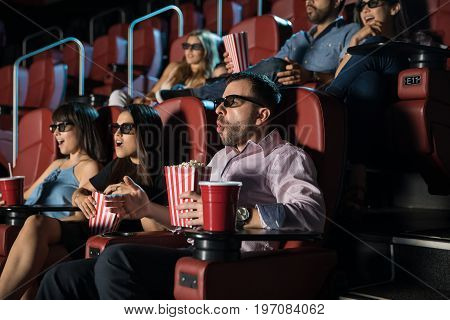 Group of young adults wearing 3d glasses and looking surprised while watching a movie at the cinema theater