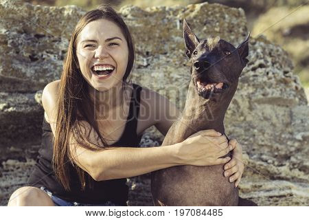 Cheerful pretty young girl sitting and hugging her dog xoloitzcuintli on the stoun beach at sunset