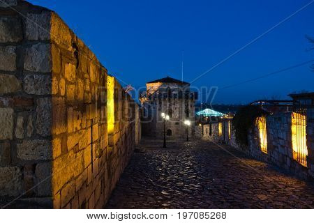 Narrow cobblestone path with an old fashioned lanterns inside Kalemegdan fortress at blue hour, Belgrade, Serbia