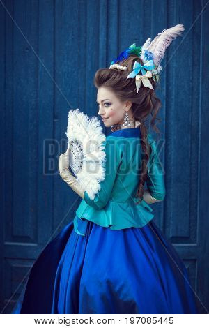 Beautiful caucasian girl dressed in the style of the Renaissance. Photo in blue tones