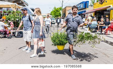 Montreal, Canada - May 28, 2017: Man Walking By Produce Vegetable Stands Outside Jean-talon Farmers