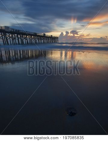 Reflection of sunrise on wet sand at the pier in Flagler Beach Florida.