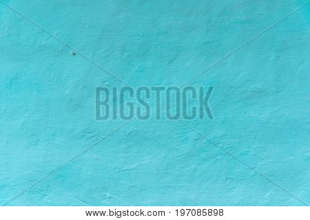 Wall whitewashed by lime azure color nail at wall textured background. Ukraine