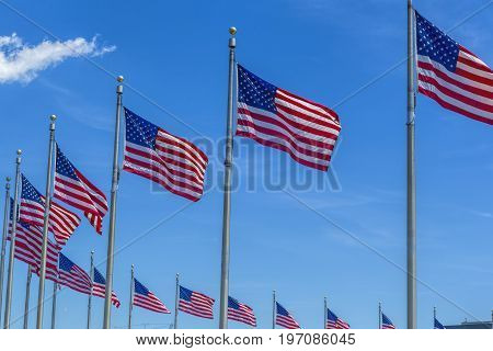 American flags on flag poles against a blue sky wave in the wind.