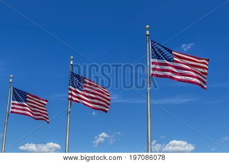 Three US flags and bright blue sky wave in the wind.