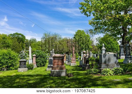Montreal Canada - May 28 2017: Cemetery on Mont Royal with grave tombstones signs during bright sunny day in Quebec region city