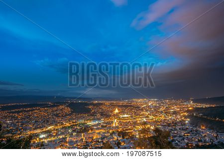 Tbilisi, Georgia. Picturesque Panoramic Aerial Cityscape In Bright Yellow Evening Illumination Under Dramatic Blue Sky In Summer Twilight.